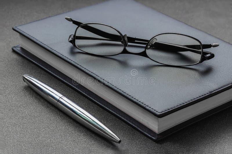 Mettez les verres et le stylo sur un carnet image stock