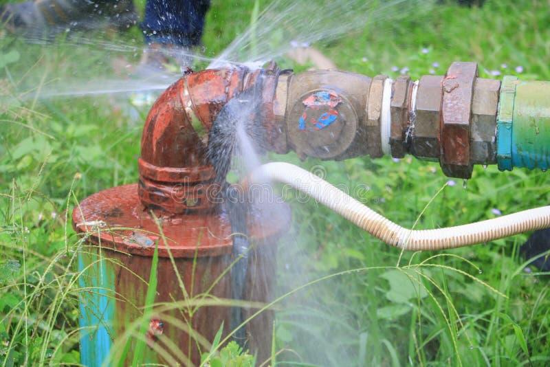 Mettre d'aplomb la fuite principale de tube et d'eau, rouille en acier de vieux tuyau de robinet sur le plancher d'herbe photographie stock libre de droits