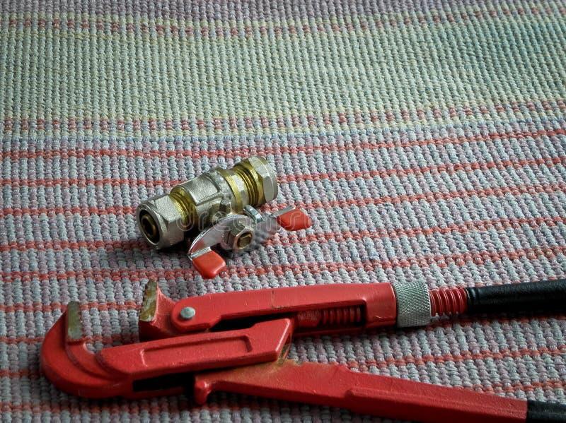 Mettre d'aplomb les outils, la clé à tube et le robinet photographie stock