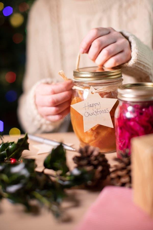 Mettre Un Balise Cadeau En Bois Réutilisable Sur Des Bocaux De Fruits Consacrés À La Maison Pour Un Cadeau De Noël Éco photos stock