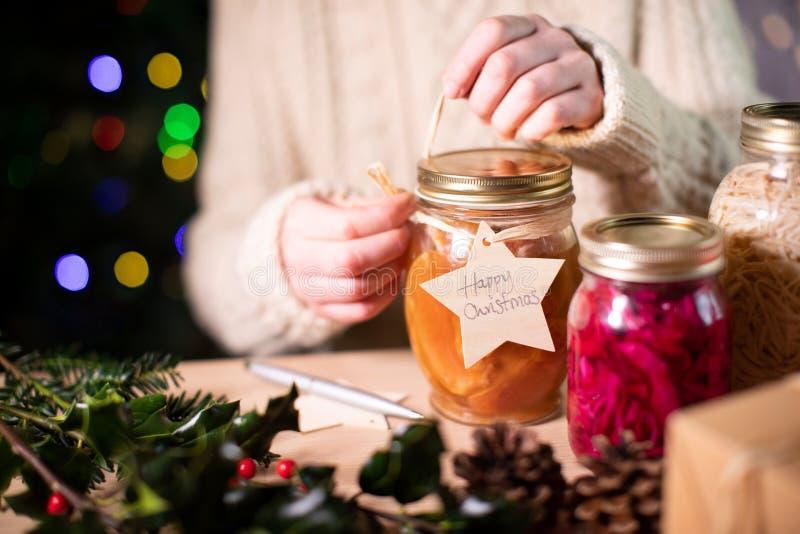 Mettre Un Balise Cadeau En Bois Réutilisable Sur Des Bocaux De Fruits Consacrés À La Maison Pour Un Cadeau De Noël Éco images libres de droits