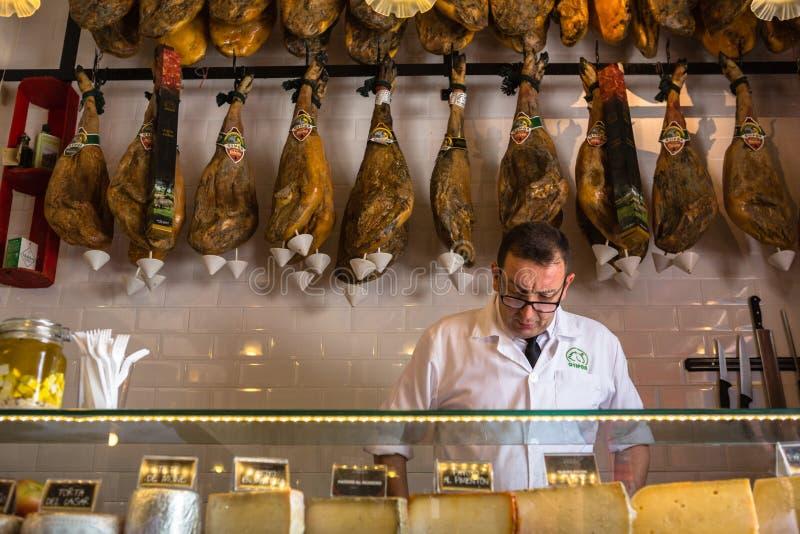 Metzger steht vor einer Wand von jamon stockfotos