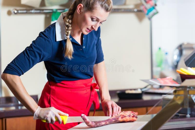 Metzgerfrau, die Rippenstückfleisch in ihrem Shop schneidet lizenzfreie stockfotos