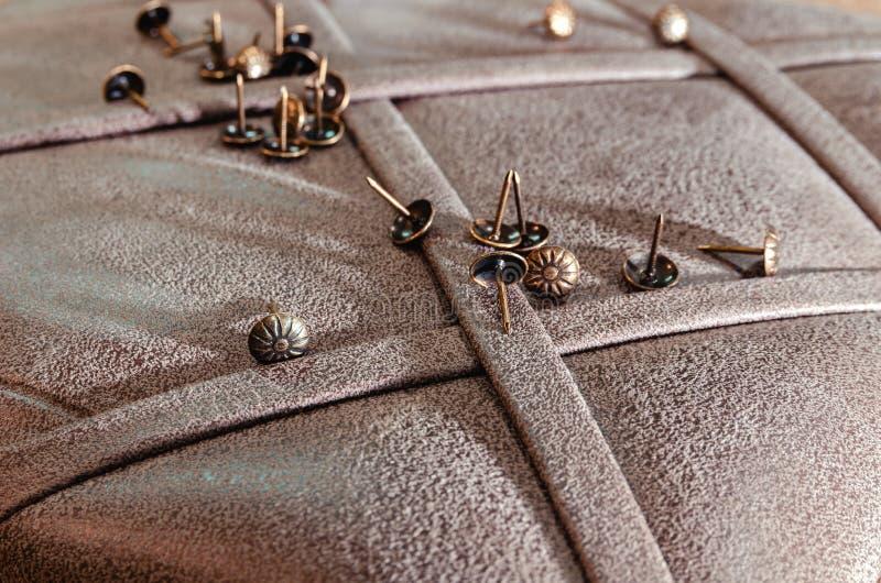 Meubilair decoratieve spijkers op de achtergrond van stoffenstoffering stock foto's