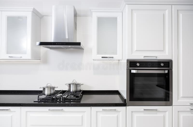 Meubles brillants blancs de cuisine avec l'équipement et les pots sur un cuiseur photo stock