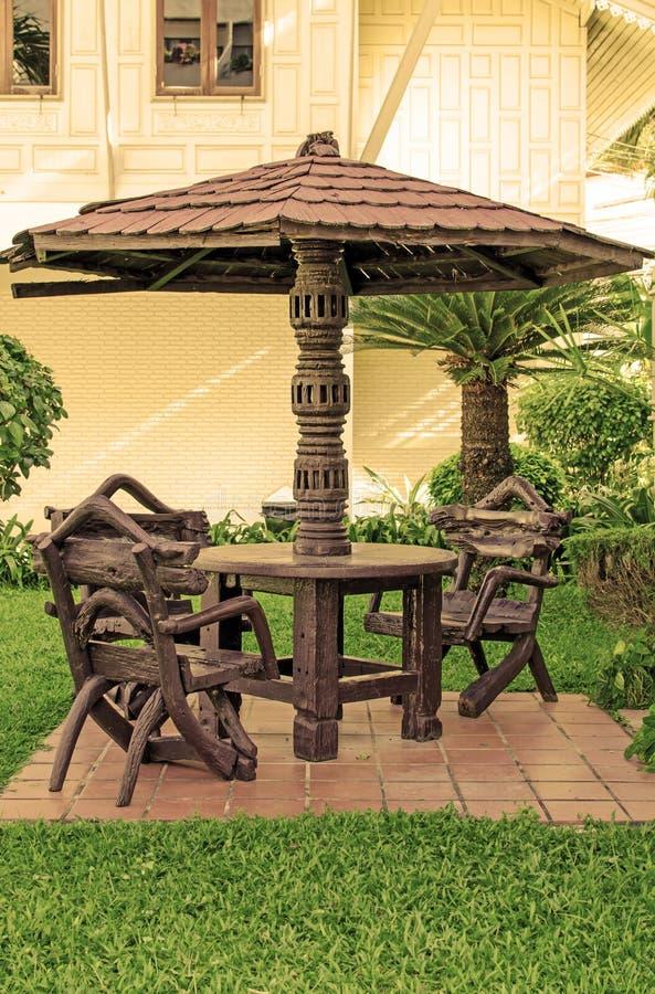 Meubles de jardin chaises et table sous le parapluie en bois chez le Gard photographie stock