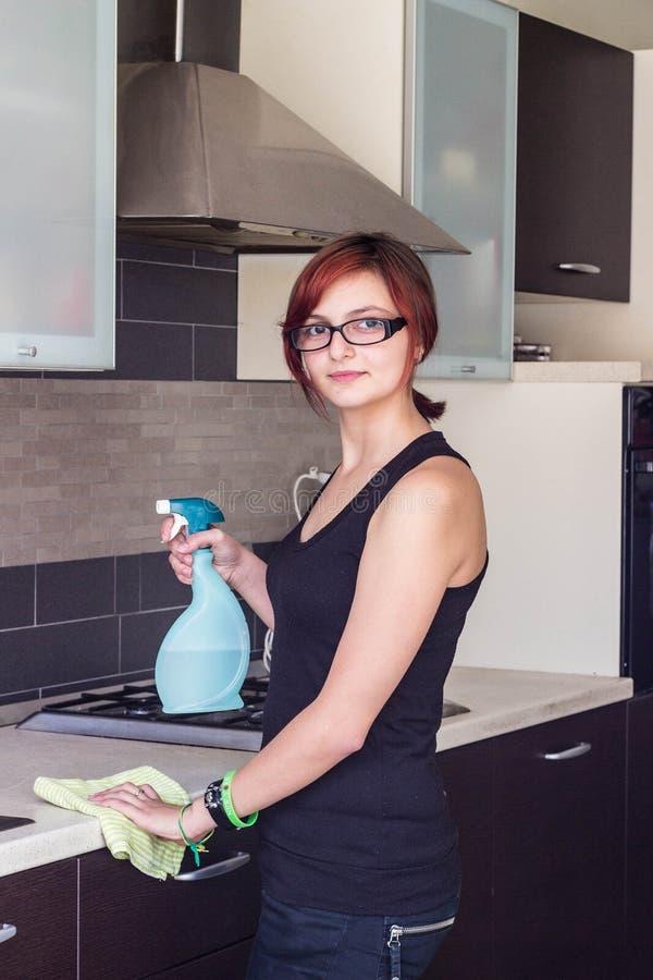 Meubles de nettoyage de jeune fille dans la cuisine image stock
