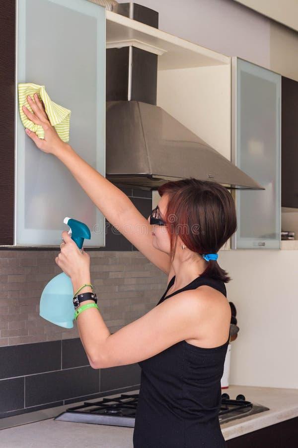 Meubles de nettoyage de jeune fille dans la cuisine image libre de droits