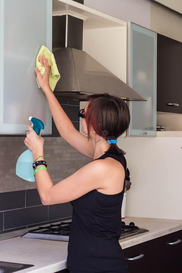 Meubles de nettoyage de jeune fille dans la cuisine photo stock
