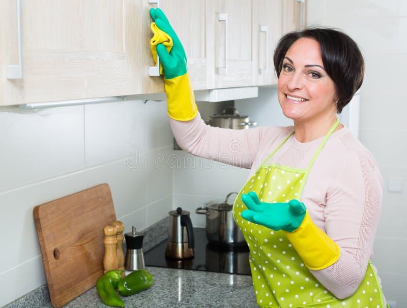Meubles de saupoudrage de femme âgés par milieu dans la cuisine image libre de droits