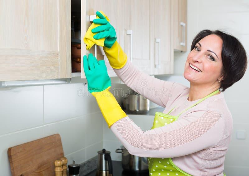 Meubles de saupoudrage de femme âgés par milieu dans la cuisine photos stock