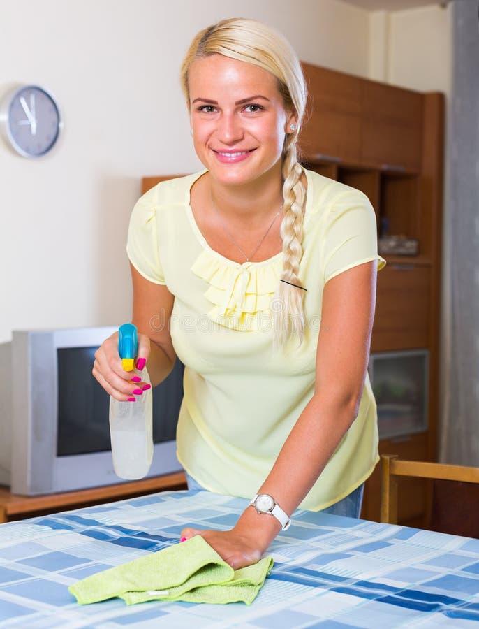 Meubles de saupoudrage de femme au foyer à la maison photographie stock