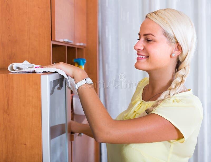 Meubles de saupoudrage de femme au foyer à la maison photos libres de droits