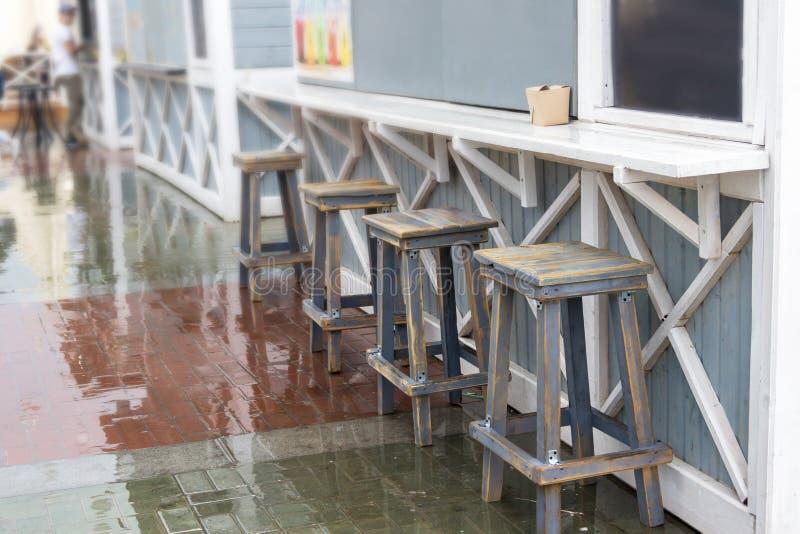 Meubles en bois sur une plate-forme en bois sur le trottoir près du café et le restaurant avec personne autour pendant un temps d photos stock