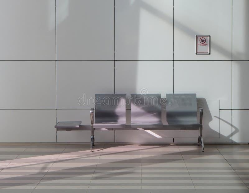 Meubles publics métalliques pour à l'intérieur Allocation des places pour trois personnes de banc sur un fond intérieur minimalis photos libres de droits