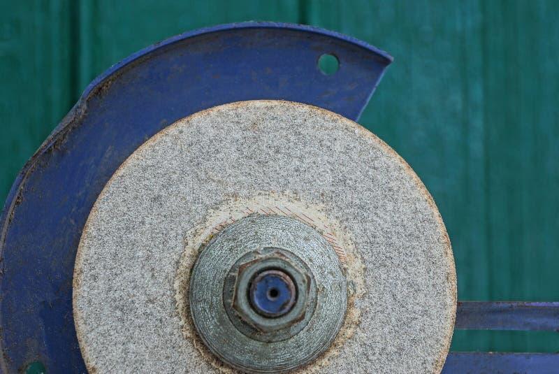 Meule en pierre grise sur une machine en métal contre un mur vert photo libre de droits