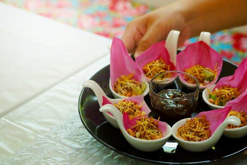 ` Meung Kum kleeb Bua `泰国传统开胃菜由Roasted许多椰子的混合做用包裹与桃红色莲花的泰国草本 免版税库存照片
