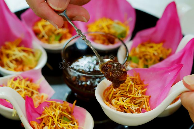 `Meung kleeb Bua` Thailand traditional appetizer make by Roasted coconut mix with many Thai herb wrapping with pink lotus. `Meung kleeb Bua` Thailand royal royalty free stock image