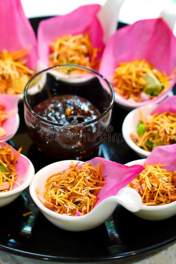 `Meung kleeb Bua` Thailand traditional appetizer make by Roasted coconut mix with many Thai herb wrapping with pink lotus. `Meung kleeb Bua` Thailand royal stock images