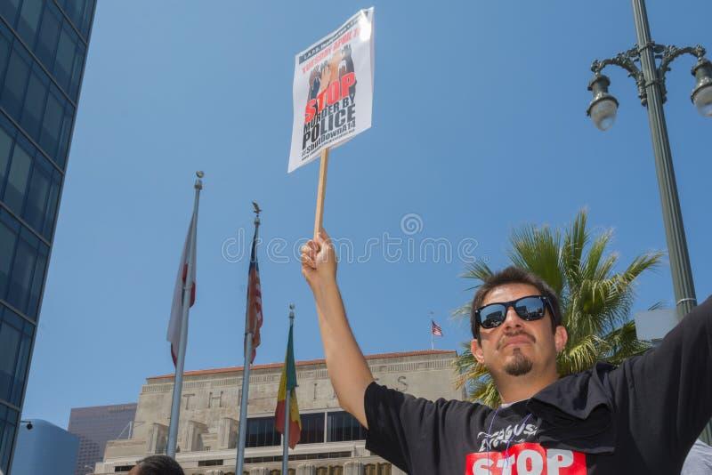 Meurtre de port d'arrêt d'homme par la chemise de police et le signe de se tenir photo libre de droits