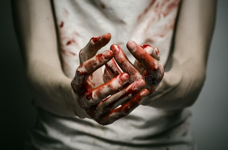Meurtrier solitaire de thème ensanglanté : le meurtrier montre les mains ensanglantées et dépression et douleur d'expérience photographie stock libre de droits