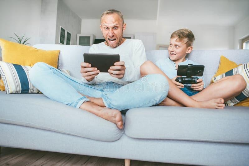 Meus divertimentos do pai dos jogos do PC apenas como mim Pai e filho que jogam emocionalmente com dispositivos eletrónicos: asse fotos de stock royalty free