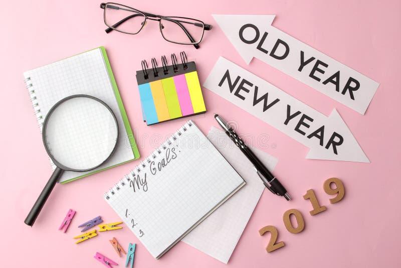 Meus objetivos 2019 texto em um caderno com etiquetas coloridas e uma pena, vidros, lente de aumento em um fundo cor-de-rosa bril foto de stock royalty free