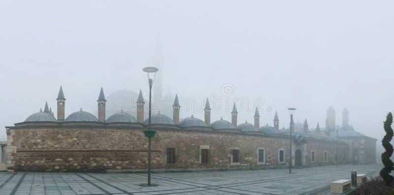 Mevlana Museum in mist. The silhouette of Mevlana Museum is hidden under the hard winter mist, Konya, Turkey stock image