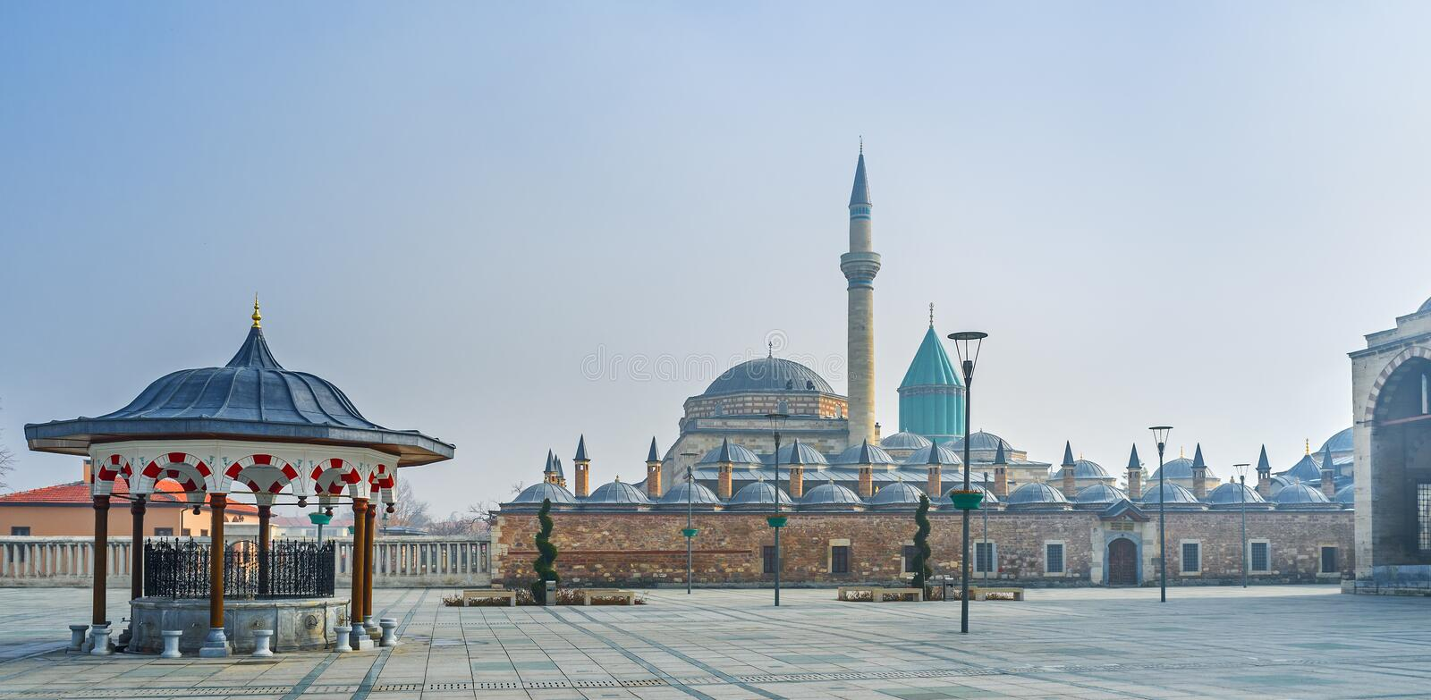 The Mevlana square. The panoramic view of the Mevlana Museum in light morning haze with the beautiful ablution fountain on the foreground, Konya, Turkey royalty free stock photo