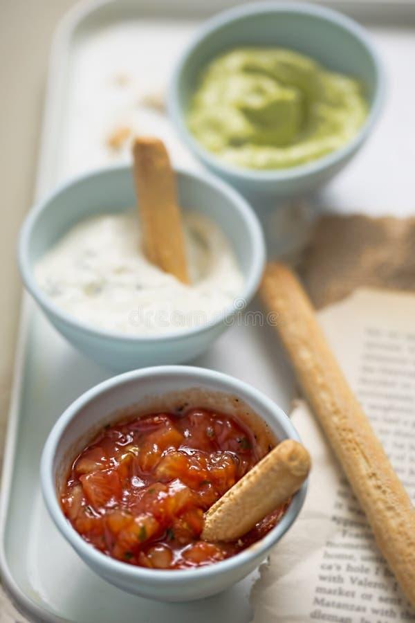 Mex de Tex - a salsa, o creme de leite com cebolinha e os mergulhos do abacate serviram com varas de pão fotografia de stock royalty free