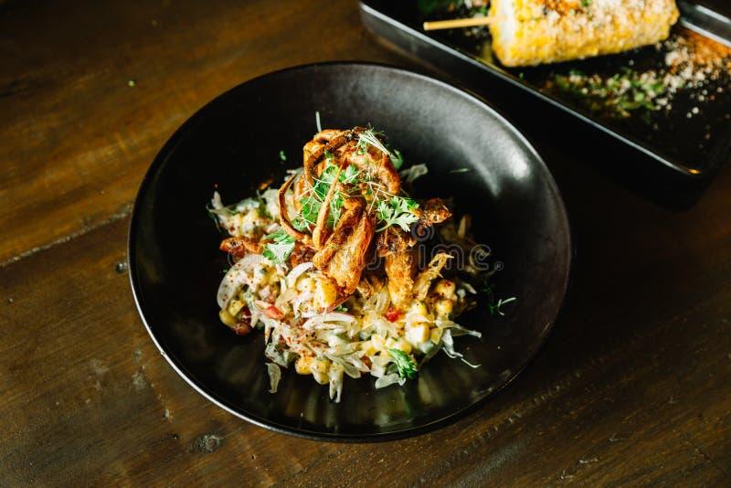 Mexicaans de saladebovenste laagje van de stijlpompelmoes met gefrituurde zachte shell krab in zwarte plaat stock afbeelding