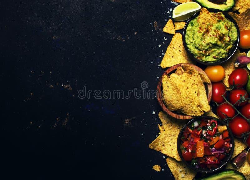 Mexicaans Voedselconcept, Nachos, Guacamole, Salsa-Saus, Zwarte Rug stock afbeeldingen