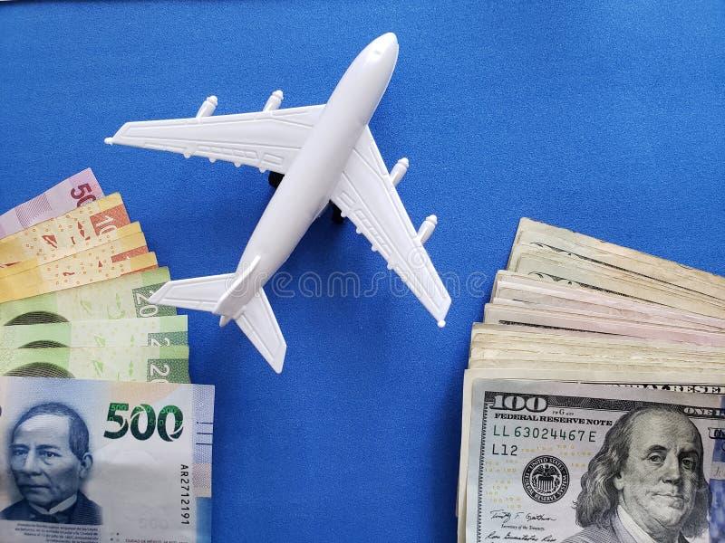 Mexicaanse bankbiljetten, wit vliegtuigcijfer, Amerikaanse dollarsrekeningen en blauwe achtergrond stock fotografie