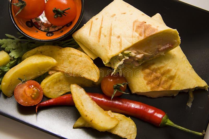 Mexicaanse die burrito met aardappel en Spaanse pepers wordt gediend stock afbeelding