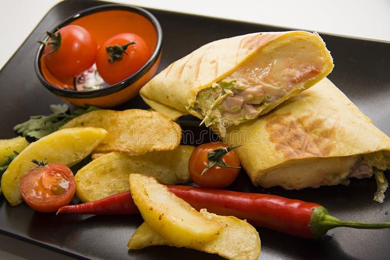 Mexicaanse die burrito met aardappel, tomaat en Spaanse pepers wordt gediend stock afbeelding