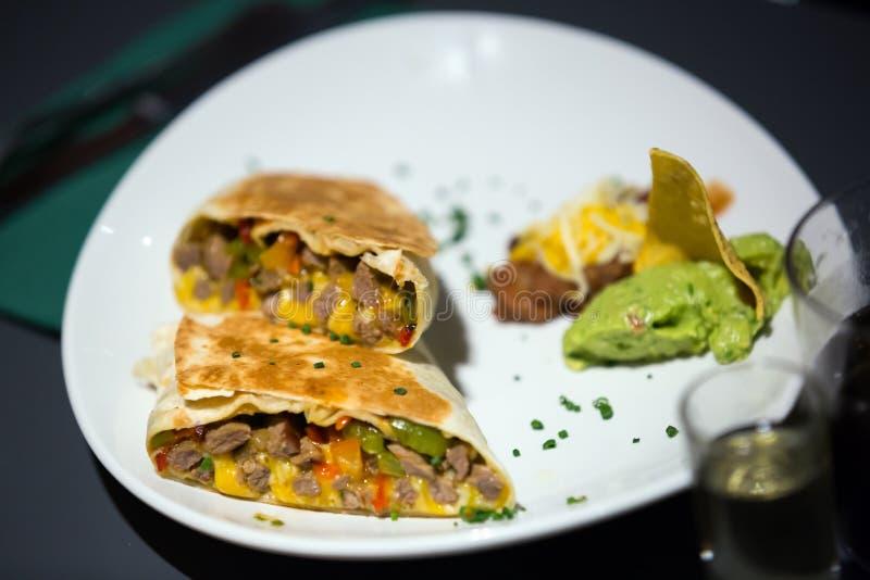 Mexicaanse die burrito met guacamole op plaat wordt gediend royalty-vrije stock fotografie