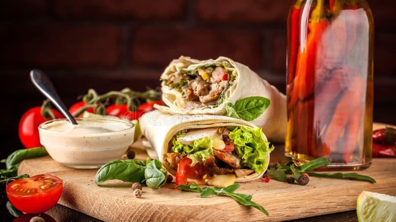 Mexicaanse keuken, burrito met kip, kersentomaten, sla, paddestoelen, rucola en Spaanse peperpeper, op een zwarte achtergrond stock foto