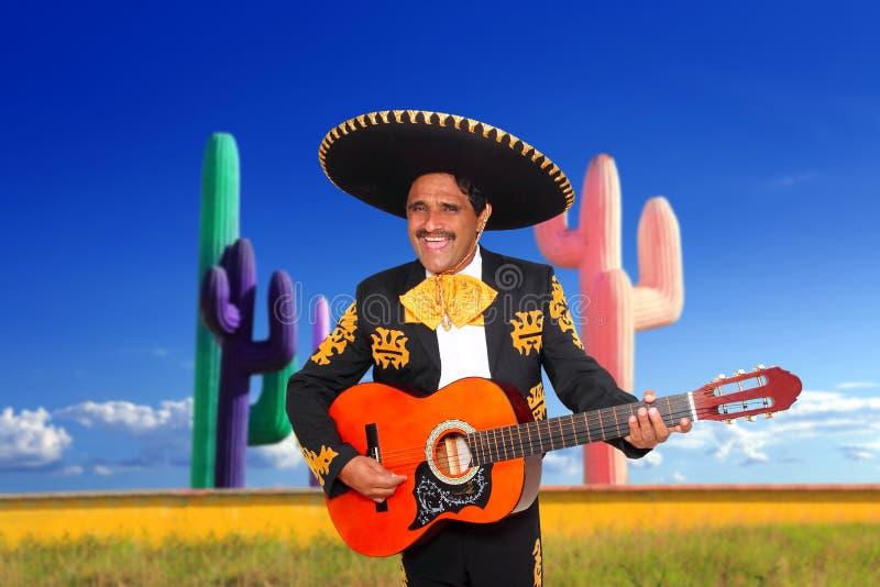 Mexicaanse mariachicharro het spelen gitaar in cactus stock afbeeldingen