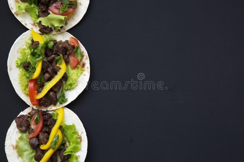 Mexicaanse taco's met rundvlees en verse groenten op een zwarte achtergrond, hoogste mening De ruimte van het exemplaar stock fotografie
