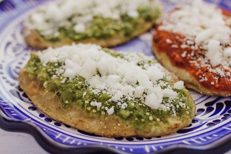 Mexicaanse tlacoyos met groene en rode saus, Traditioneel voedsel in Mexico stock fotografie