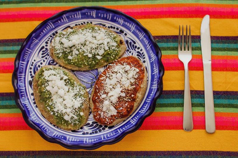 Mexicaanse tlacoyos met groene en rode saus, Traditioneel voedsel in Mexico royalty-vrije stock fotografie