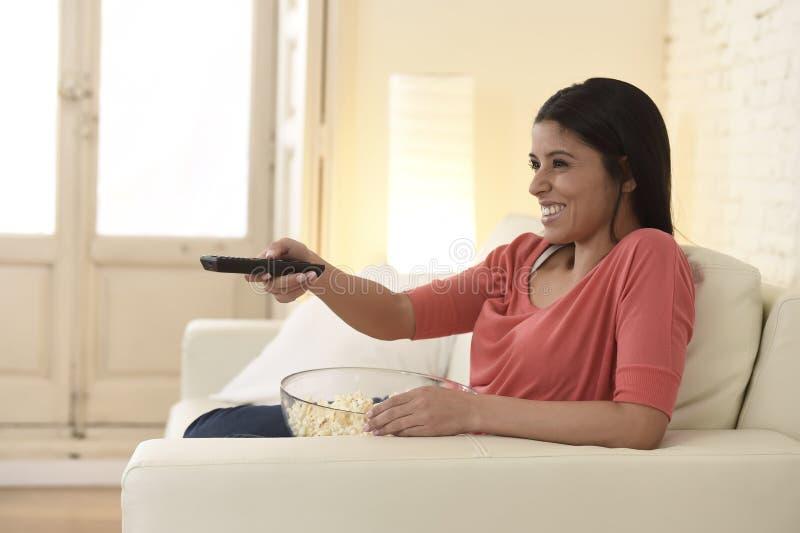 Mexicaanse vrouw het letten op televisie bij banklaag gelukkige opgewekte het genieten van romantische film royalty-vrije stock foto