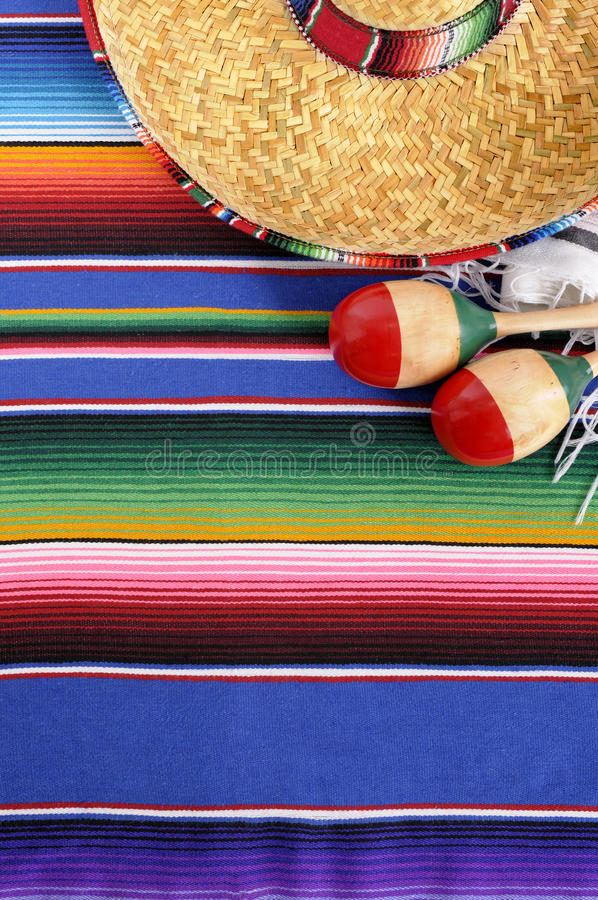 Mexico : Mexican sombrero blanket background, copy space vertical. Mexican background with sombrero straw hat, maracas and traditional serape blanket or rug stock image