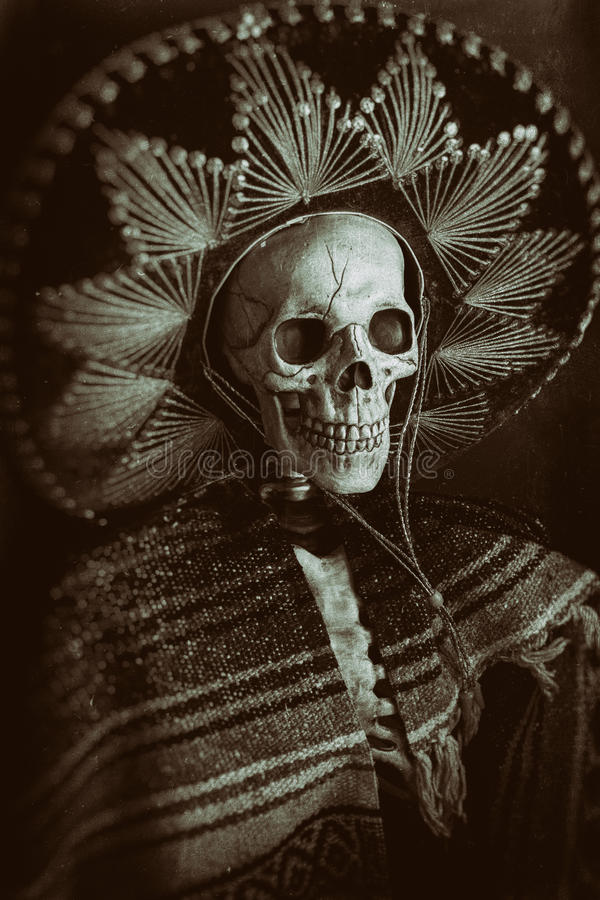 Mexican Bandit Skeleton. A skeleton wearing a Mexican sombrero and a poncho. Edited in a vintage film style stock photography
