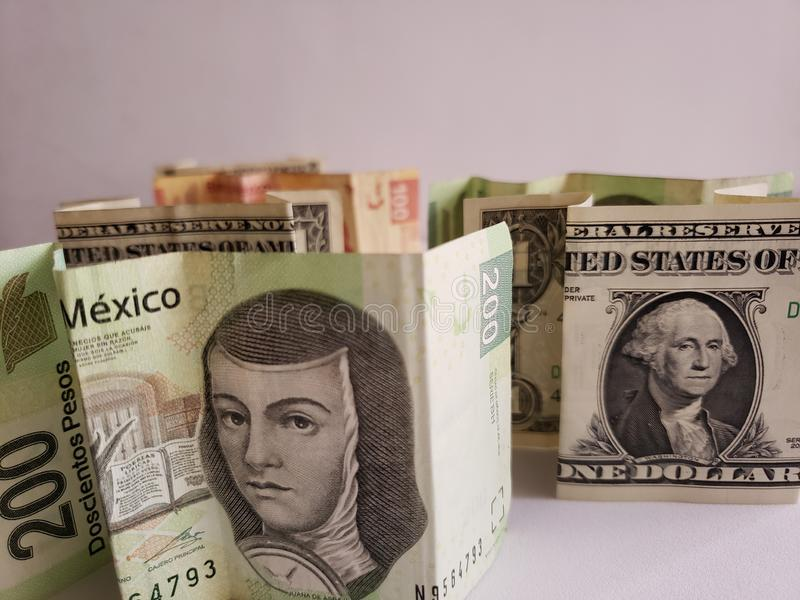 Mexican banknotes and American dollar bills stock photos