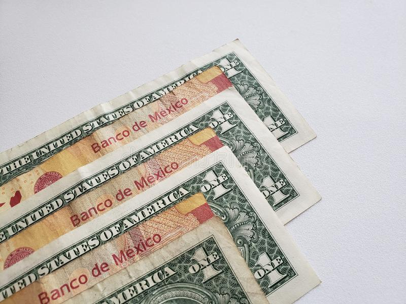 Mexican banknotes and american one dollar bills on white background royalty free stock photo