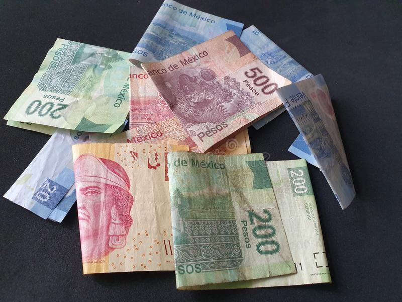 Mexican banknotes of different denominations unorganized. Commerce, exchange, trade, trading, value, buy, sell, profit, price, rate, cash, currency, paper stock images
