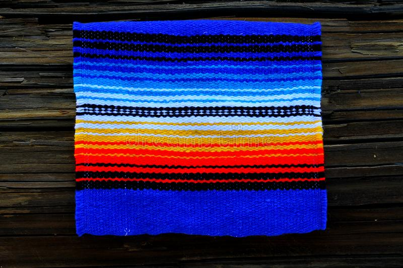 Mexican blanket background Cinco de Mayo. This Mexican blanket is displayed on a wood background and is perfect for displaying your copy regarding a holiday in royalty free stock photo