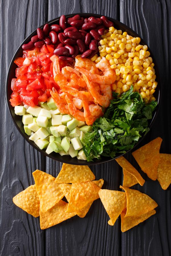 Mexican burrito bowl with shrimp, beans, corn, avocado and herbs stock image