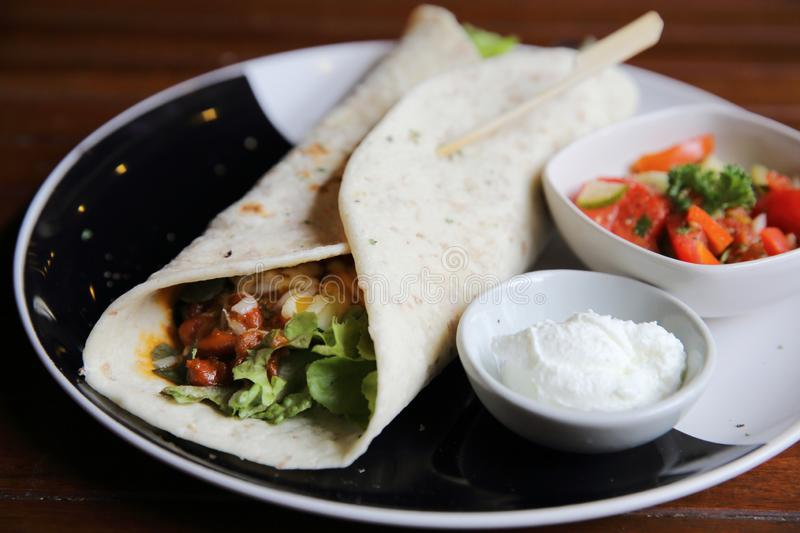 Mexican burritos on a plate with tomato salad. In close up royalty free stock photo